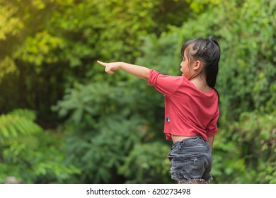 Asian girl child in Red T-shirt wags the trees