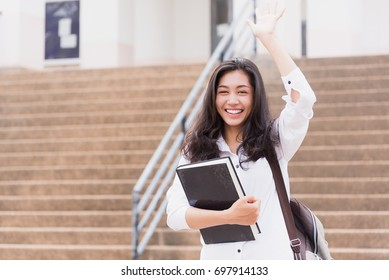 Asian girl college student smiling happily holding her books standing on a campus and waving hello friends ,learning, education and school concept