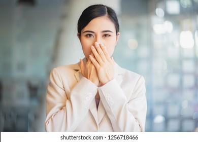Asian girl covering her mouth don't speak not talking.