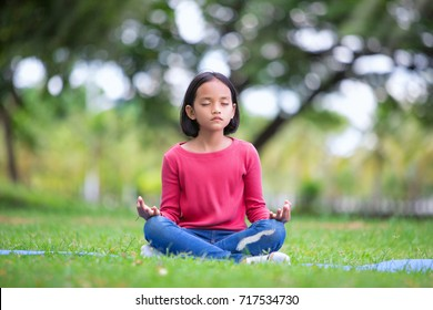 asian girl doing yoga pose in the park outdoor
