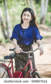 Asian girl dressed in traditional local and her bicycle in the countryside.