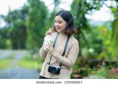 Asian girl is drinking green tea with straw in the garden