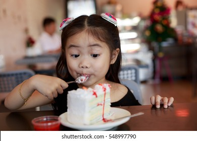 Asian girl eating cake in restaurant.