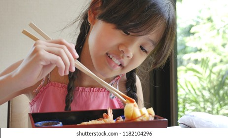 Asian girl eating Japanese food sushi in a restaurant, Sushi is a traditional food of Japan