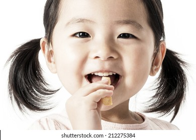 A asian girl eating snacks.