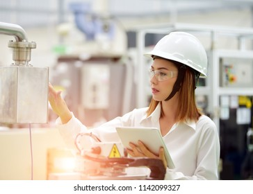 Asian girl engineer wearing a safety helmet and a white safety helmet.while working with a laptop for Machine Controller in the factory , the expression is serious face.