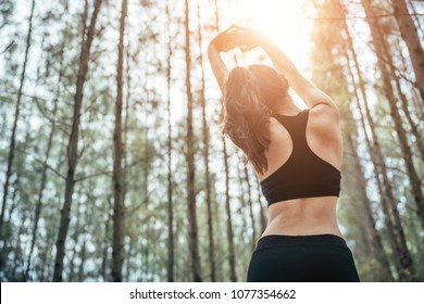 Asian girl is exercising at the weekend in a pine forest green and lush beautiful. Sport girl and lifestyle concept. She also playing yoga.