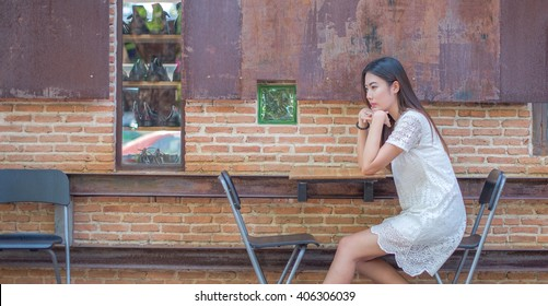 Asian girl feel comfortable on chair in front of building