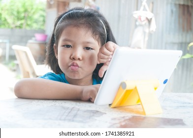 Asian Girl feeling unhappy while learning online course or playing game online on Digital Wireless Device or Tablet at home as Technology e-learning concept.
