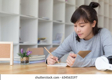 asian girl female teenager studying at school. Student writing note in cafe - education, people and learning concept