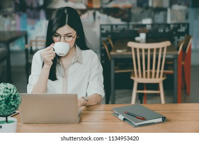 An Asian girl is freelancer woman, she is working by using the laptop computer and driking a cup of coffee on morning in a coffee shop or her office.