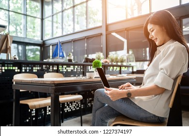 Asian girl is freelancer woman, she is working by using the laptop computer and driking a cup of coffee on morning in a coffee shop or her office.