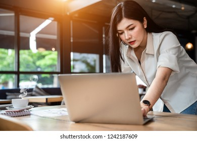 An Asian girl is freelancer woman, she is working by using the laptop computer  on morning in a coffee shop or her office. She is using the smart phone. Small business concept.