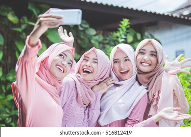 asian girl friends with head scarf taking selfie together