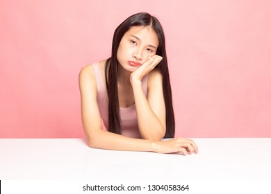 Asian girl is getting bore on pink background