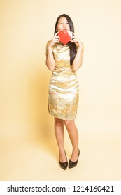 Asian girl in golden chinese cheongsam dress  on beige background