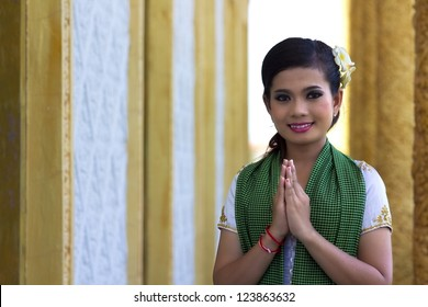 Asian Girl Greets in temple traditional way with both hands