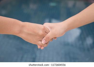 Asian girl handshake with pleasure.