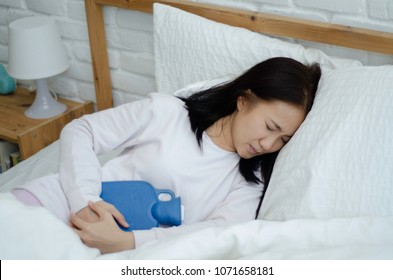 Asian girl has abdominal pain and use a hot water bag embrace to relieve symptoms.