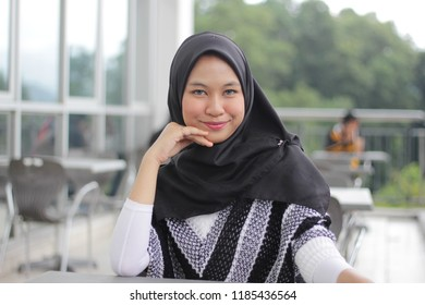 Asian girl having a drink and relax. Girl wearing black hijab