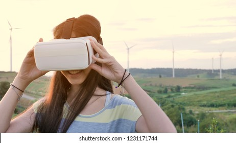 Asian girl having fun with virtual reality glasses while standing in win generators
