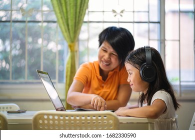 Asian girl and her teacher using laptop for online study during homeschooling at home. homeschooling, online study, home quarantine, online learning, education, corona virus or online technology