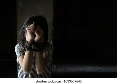 Asian girl with his hands tied in an abandoned building,stop abusing violence,human trafficking concept