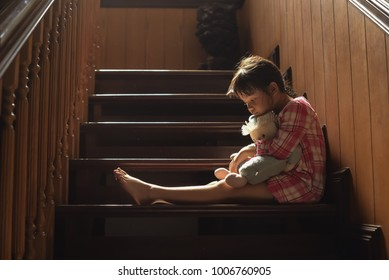 Asian girl hold her doll and cry or scare or sad or feel bad. on the staircase