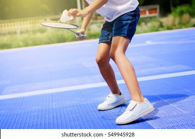 Asian girl holding badminton racket and shuttlecock at court