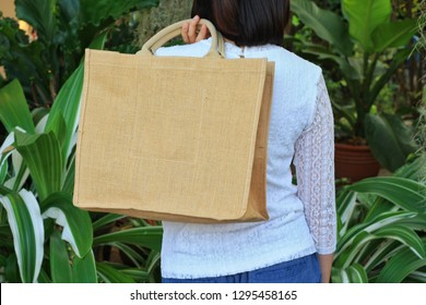 Asian girl holding  blank linen nature canvas tote bag for mock up design. On green garden background.Use tote bag for Replacement plastic bag can save the earth.Reduce global warming concept.