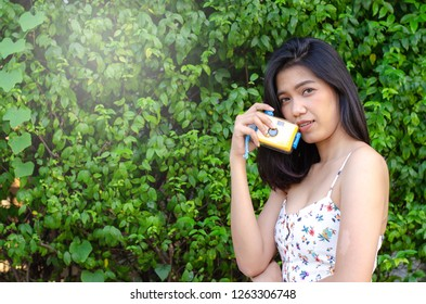 asian girl holding camera against green plant
