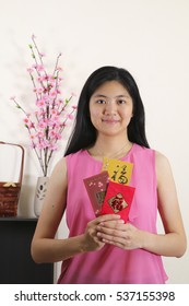 Asian girl holding chinese new year angpow packets with chinese greeting for Chinese new year. 2017 is known as the year of the chicken according to chinese zodiac.