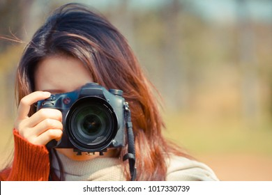 Asian girl holding a digital camer with copy space to add text