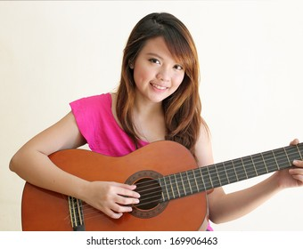 Asian Girl Holding a Guitar