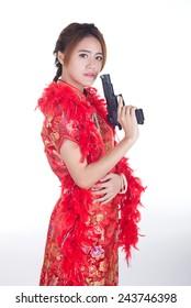 Asian girl holding Handgun in Chinese dress traditional