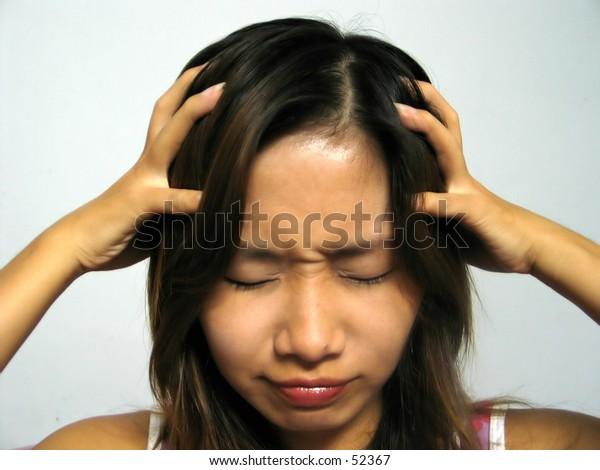 an asian girl holding her head...she's got a headache