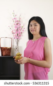 Asian girl holding mock gold ingot as greeting for chinese new year