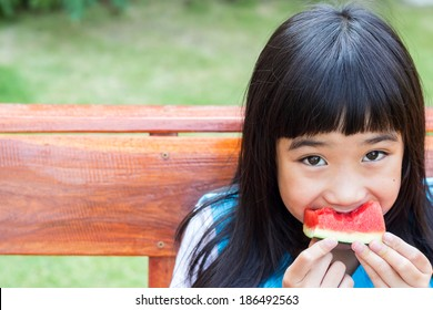 Asian girl holding slice of watermelon