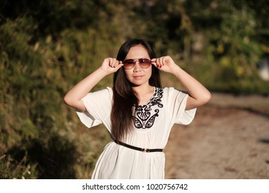 Asian girl holding sunglasses with both hands in summertime.