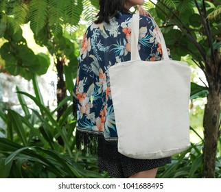 asian girl holding white blank linen nature canvas tote bag for mock up design. On tropical background