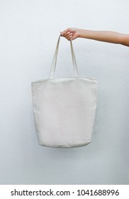 asian girl holding white blank linen nature canvas tote bag for mock up design. On white background