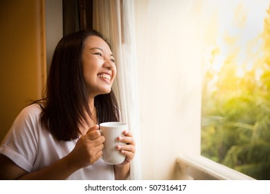 Asian girl holding white cup of coffee feeling relax and look outside window in morning time