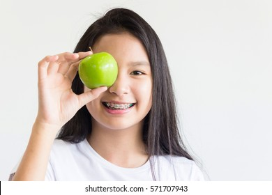 asian girl holds a green apple on her eye and smiles with braces