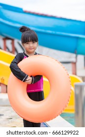 Asian girl holds rubber ring in swimming pool.