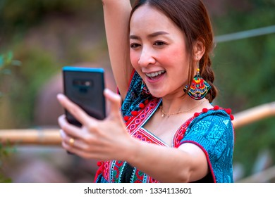asian girl in holiday by posing smile relaxation take a selfie photo in nature mountain and watercourse by wearing lanna dress north thailand