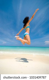 asian girl jumping in joy on a beach
