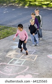 Asian girl jumping on hopscotch board with friends watching.  Ages 7 to 9