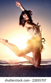 Asian girl jumps high on beach with sun in background