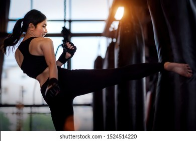 Asian girl kick a sand bag in kickboxing gym, this image can use for fitness, sport, exercise and muy thai concept