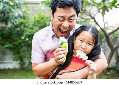 Asian girl kid and her father eatting ice cream in the garden.